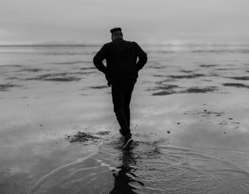 Man with depression walking on beach